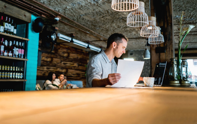 Male business owner working at a restaurant doing the books - entrepreneurship concepts