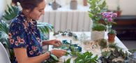 Young beautiful woman creating making christmas decorations, crafting xmas wreaths