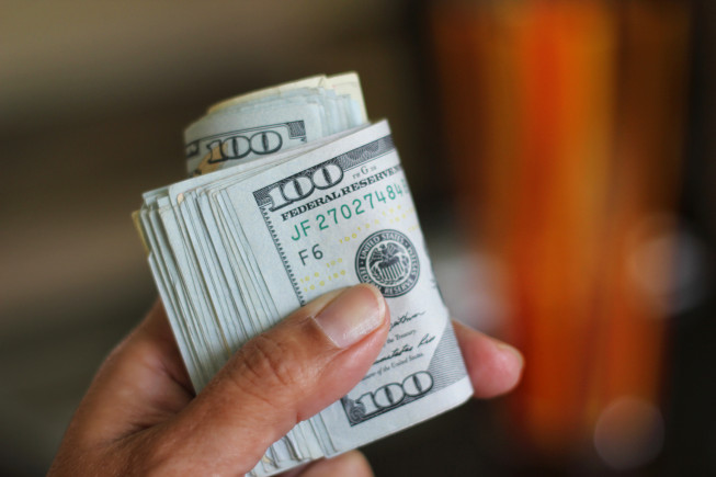 Hand holds roll of 100 dollar bills