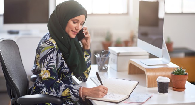 Successful confident businesswoman in headscarf taking notes while on phone working in modern office