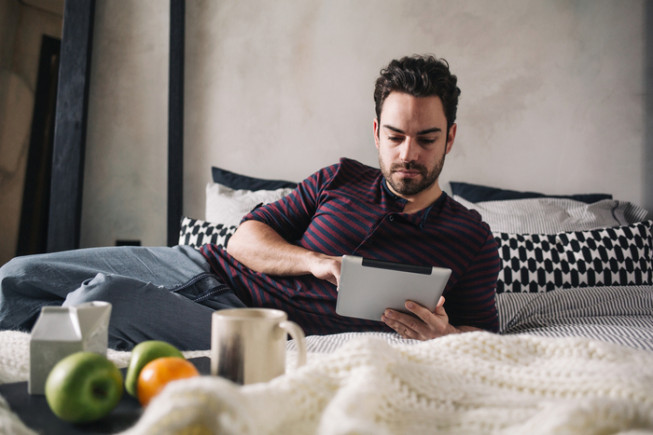 Morning routine: a man  using his digital tablet in bed in the morning.