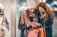 Friends walking on city street by night. Checking smart phone to see which shops thay pick. Holding shopping bags. Wearing warm clothing.