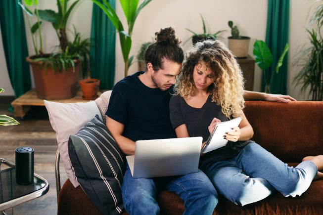 Woman and man working together sitting on couch in living room.