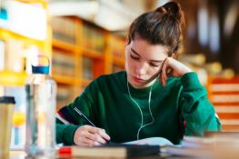 Young woman with earphone studying on library.