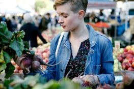 A beautiful young woman looks closely at a bunch of beets at a farmers market
