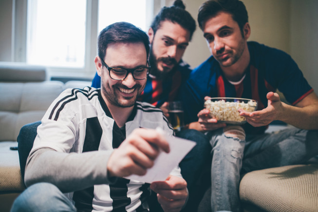 Soccer enthusiasts looking at betting slip