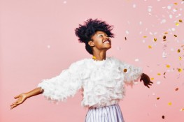 Portrait of a young girl with a big smile throwing confetti in the air, isolated on pink studio background