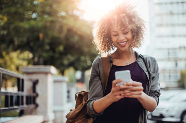 Picture of a young smiling woman using a phone