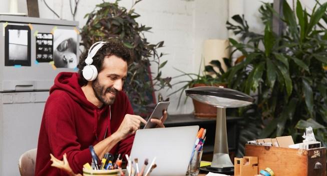 Hombre adulto sonriente usando tecnologías en la mesa del estudio del artista