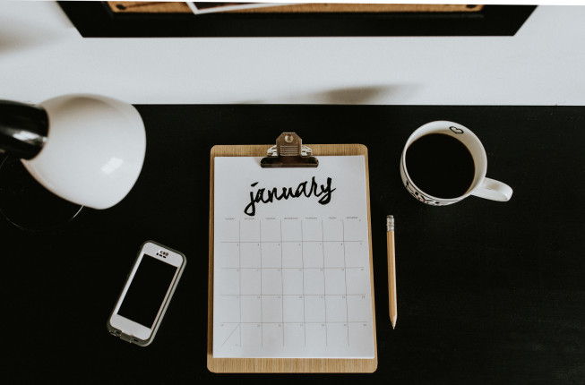 A calendar for the new month sitting on a desk preparing for the upcoming year