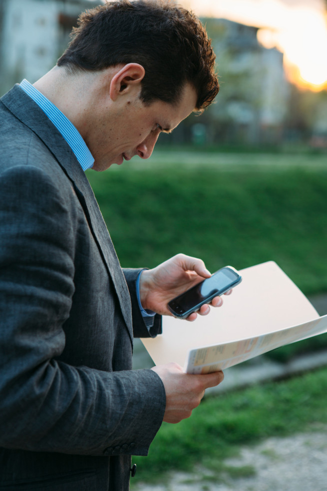 Businessman Holding Documents And Cellhphone Outdoors