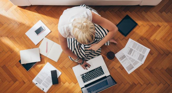 Mujer de negocios sentada en el suelo y trabajando en un ambiente relajado.