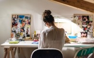 Young businesswoman at her desk in home studio.