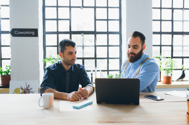 Two businessman working and sitting in front of a laptop.