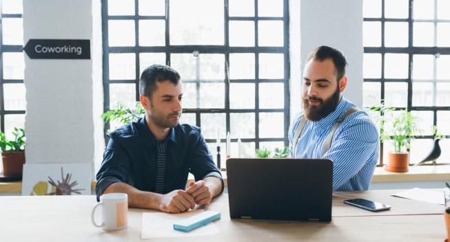 Dos hombres de negocios trabajando y sentados frente a una computadora portátil.