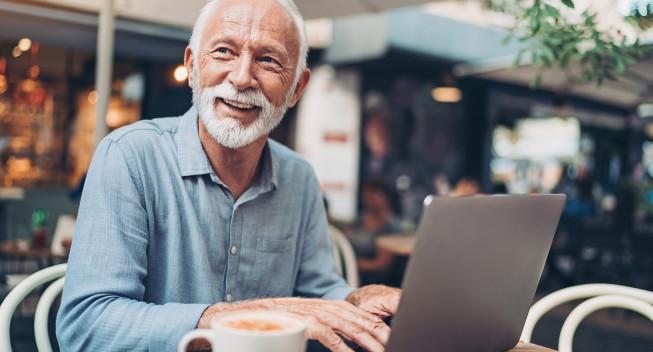Un hombre mayor usando un portátil para verificar su identidad.