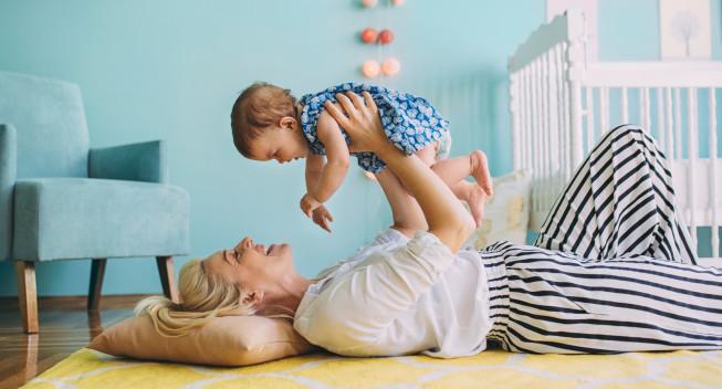 La niñera acostada en el suelo y sosteniendo a una niña