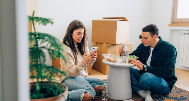 Love couple sitting in a new apartment, eating, having a break