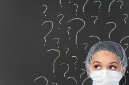Female doctor thinking in front of question marks