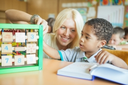 Learning Numbers: First Grader and His Teacher in Class