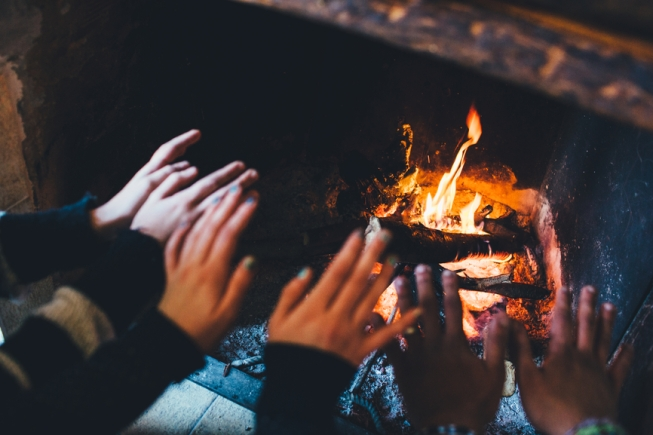 Hands warming themselves by the fire