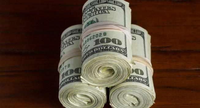 Three rolls of US one hundred dollar bills