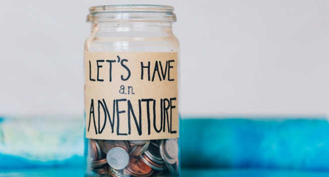 """Money jar with coins on atlas labelled """"Let's Have An Adventure"""""""