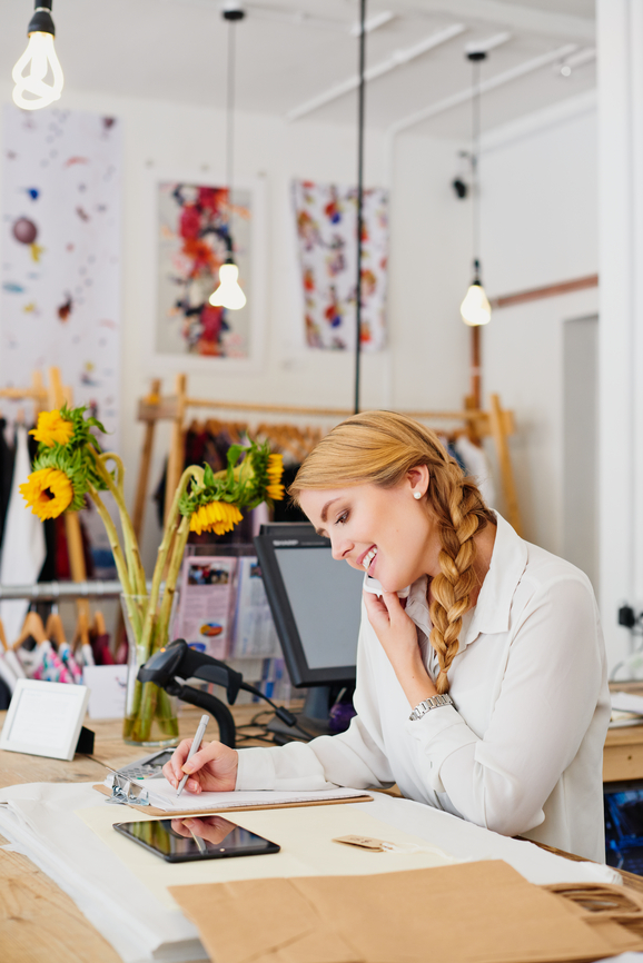 Small business owner on the phone in her clothing boutique