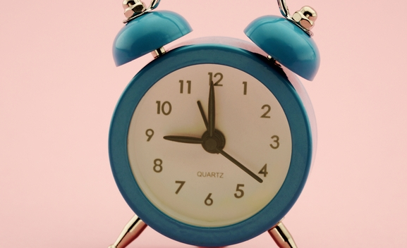 Small alarm clock and background  in pastel colors with copy space