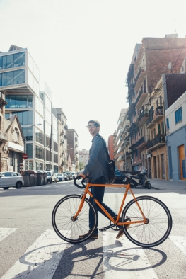 Young man walking with his bike in Barcelona