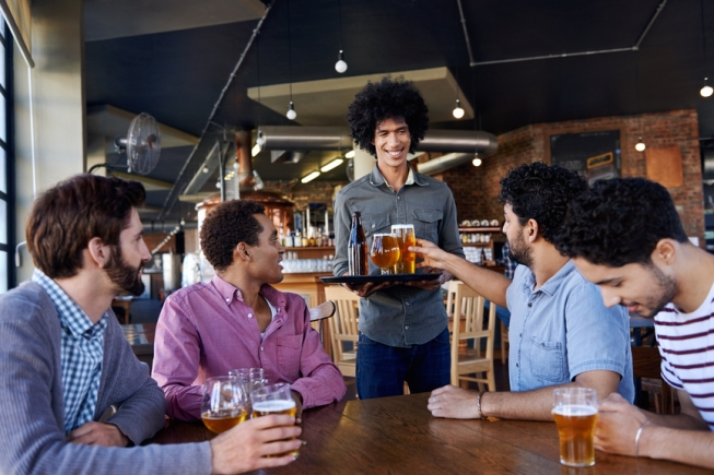 waiter in trendy hipster brewery pub bringing tray of craft draught beer pints to table of friends at happy hour