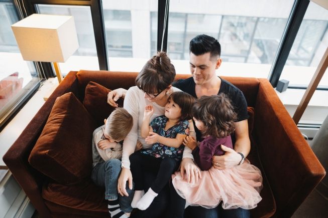 Young family of five sitting together on couch having fun tickli