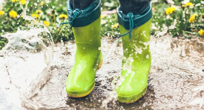 Legs of a boy in green rubber boots splashing in a puddle.