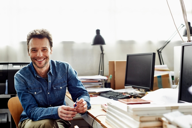 Portrait of smiling businessman sitting at desk in office