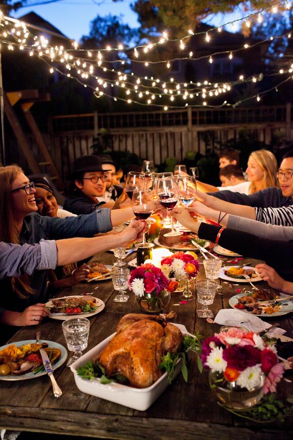 Friends enjoying dinner outside, raising their glass for a toast.
