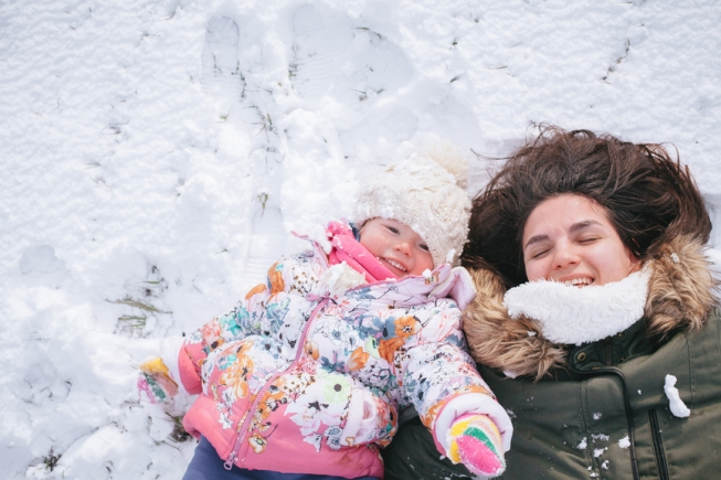 Mother and daughter playing in the snow
