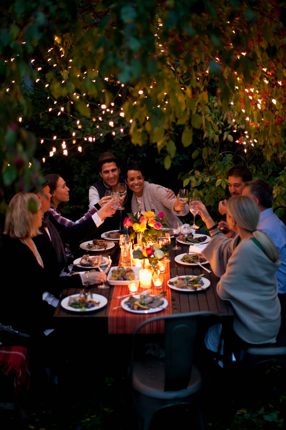 Friends gather for outdoor dinner party, underneath a weeping cherry tree.
