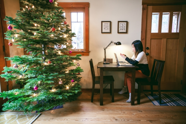 Vietnamese woman in her late 20's working on her computer at her home with a christmas tree