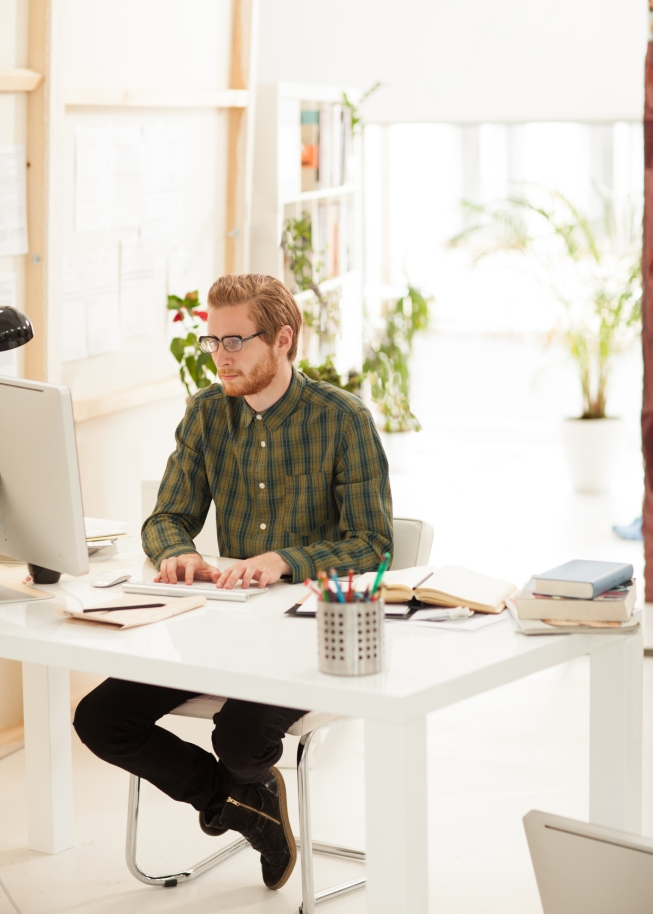 Young businessman working on the computer at his modern spacious office.