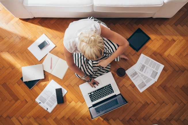 Businesswoman sitting on the floor and working in a relaxed atmosphere.