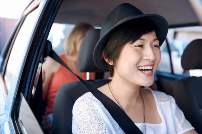 A laughing pretty chinese woman with a hat on driving somewhere with her friends in the backseat