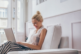 Smiling Caucasian woman sitting on her sofa and using her laptop.