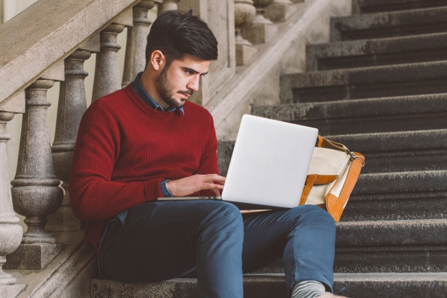 College student using his laptop on the campus.