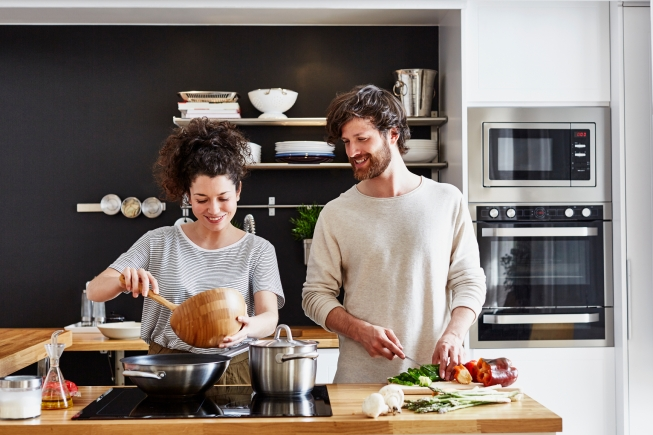 Happy young couple cooking together in kitchen