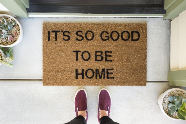 "Woman standing in front of a doormat reading ""It's so good to be home""."