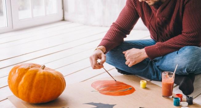 Man painting pumpkin with gouache