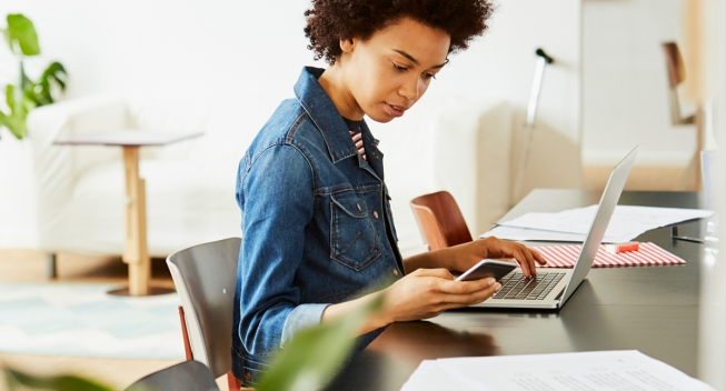 Young creative businesswoman using mobile phone and laptop at desk in office