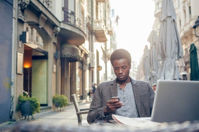 Young African man sending a text message in an outdoor cafe.