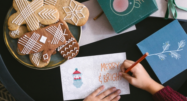 From above photo of  blonde girl writing Christmas greeting card.