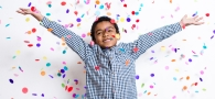 Boy celebrating filing taxes with confetti